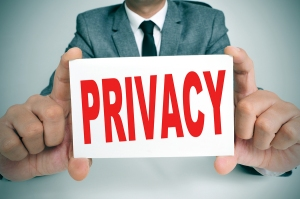 a man wearing a suit showing a signboard with the text privacy w